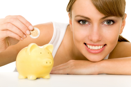 A woman dropping a coin in a piggy bank.